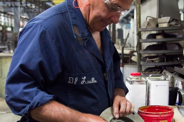 DJ Luallen paints chrome stop on a part to be chrome finished in Anniston Army Depot's Metal Finishing Branch. Chrome stop prevents the chrome from adhering to the part.