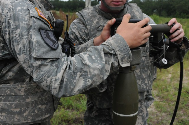 Spc. Robert Pierce and Spc. Christopher Hoffman set the fuse of an Accelerated Precision Mortar Initiative cartridge during a training exercise, Aug. 8, 2012, at Fort Stewart, Ga. The APMI round is a GPS-guided 120mm mortar that allows precision-strike capability, creating less collateral damage on the battlefield.