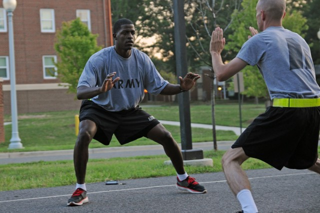 Staff Sgt. Terrell Moorer (left), Motor Transport Operator, 529th Regimental Support Company, 3d U.S. Infantry Regiment (The Old Guard), leads Staff Sgt. Patrick Hall, Wheeled Vehicle Mechanic, in a shuffle drill during physical fitness training [PT], Aug. 16, at Joint Base Myer-Henderson hall, Va. Moorer, a former All-Army Basketball player, uses the shuffle drill to help Soldiers work on their agility. (U.S. Army photo by Staff Sgt. Megan Garcia)