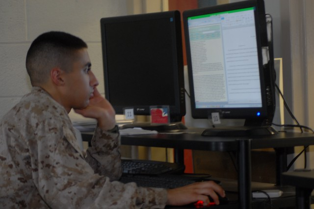 Marine Pfc. Anthony P. Rayis, a broadcasting student at the Defense Information School, works on a computer to complete his homework assignment.