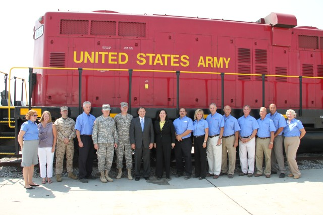 Gen. Martin E. Dempsey, chairman of the Joint Chiefs of Staff, and Katherine Hammack, assistant secretary of the Army for installations, energy and environment, pose for a group photo with the men and women of Tooele Army Depot, Utah, in front of the Army Depot's locomotive engines. Dempsey and Hammack congratulate the men and women, who for 70 years have provided readiness and rapid munitions response to America's allies and war fighters worldwide.