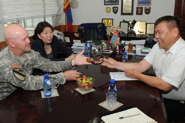 Brig. Gen. Mike Bridges, commander of the Alaska Army National Guard, exchanges gifts with Dumaa Namsrai, deputy chief, National Emergency Management Agency (NEMA), at the NEMA office in Ulaanbaatar, Mongolia, Aug. 13. Bridges attended the meeting while in Mongolia as part of the National Guard State Partnership Program (SPP). He also visited Khaan Quest, a regularly scheduled, multinational exercise sponsored by the U.S. Army Pacific (USARPAC) and hosted annually by the Mongolian Armed Forces. Khaan Quest 12 is the latest in a continuing series of exercises designed to promote regional peace and security. This exercise marks the tenth anniversary of this regionally significant training event.