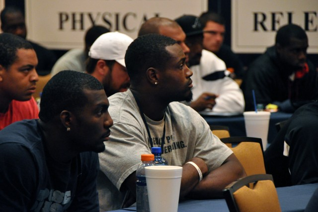 Dez Bryant, wide receiver, and Jamize Olawale, running back with the Dallas Cowboys National Football League team, listen as Gen. David M. Rodriguez, commanding general, U.S. Army Forces Command, relays the story of the combat action in Afghanistan for which Army Staff Sgt. Salvatore Giunta received the Medal of Honor.  Rodriguez visited the team's Oxnard, Calif., training camp on Aug. 15, 2012, during a trip that included training, operational and command updates at Fort Irwin, Calif., and Joint Base Lewis-McChord, Wash.