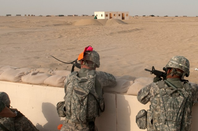 Soldiers of A Company, 4th Battalion, 118th Infantry Regiment engage targets after assaulting and clearing a trench system, one of their objectives during a platoon live-fire exercise at the Udairi Range Complex in northern Kuwait, July 31, 2012. The brightly colored material of the progress pole is visible on the Soldier to the left. As the name implies, a highly-visible progress pole shows the assault element's progress and location as they clear a trench, so troops providing fire support know where to shoot safely and effectively. The Soldiers also cleared buildings during the exercise. In addition to undertaking camp and security-force operations, the South Carolina Army National Guard Soldiers have kept up the pace of their training since deploying to Kuwait in April.