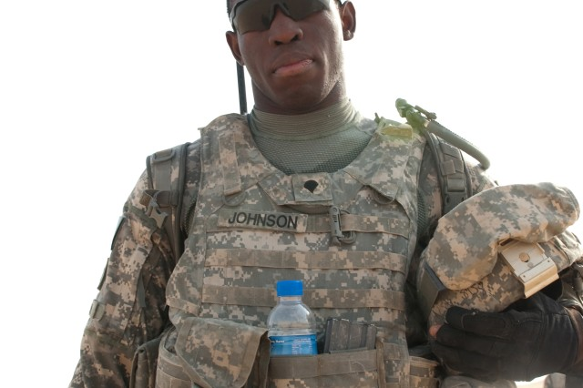 Spc. Josiah Johnson, of A Company, 4th Battalion, 118th Infantry Regiment, poses after he and other battalion Soldiers completed a platoon live-fire exercise at the Udairi Range Complex in northern Kuwait, July 31, 2012. The Soldiers assaulted and cleared buildings and a trench system during the exercise. Attached to Johnson's equipment is the highly-visible, flag-like device known as a progress pole. As the name implies, a progress pole shows the assault element's progress and location as they clear a trench, so troops providing fire support know where to shoot safely and effectively. In addition to undertaking camp and security-force operations, the South Carolina Army National Guard Soldiers have kept up the pace of their training since deploying to Kuwait in April. Johnson is from Cross, S.C.