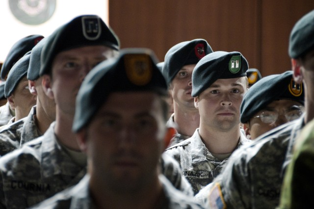 Special Forces Qualification Course graduates stand at attention while wearing their green berets for the first time at their graduation ceremony Aug. 9 in Fayetteville, N.C. (U.S. Army photo by Dave Chace, SWCS Public Affairs Office)