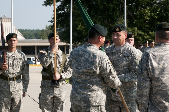 "Maj. Gen. Edward M. Reeder, Jr. (center) hands the U.S. Army John F. Kennedy Special Warfare Center and School colors back to his senior enlisted advisor, Command Sgt. Maj. Ledford ""J.R."" Stigall to complete the passing of the colors ceremony for SWCS. (U.S. Army photo by Dave Chace, SWCS Public Affairs Office)"