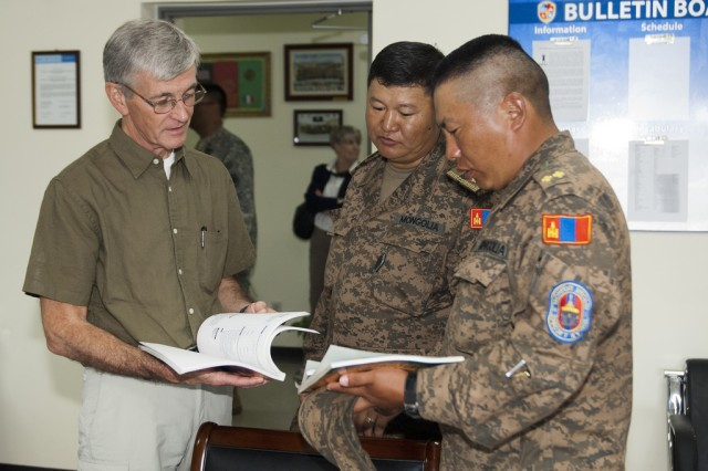 Secretary of the Army John McHugh speaks with Maj. Gen. B. Bayarmagnai, deputy chief of general staff, Mongolian Armed Forces, and an exercise participant about the various courses held during exercise Khaan Quest 2012, Aug. 15, at the Mongolian Armed Forces Peace Support Center in the vicinity of Ulaanbaatar, Mongolia, Aug. 15, 2012. Khaan Quest is regularly scheduled multinational exercise sponsored by U.S. Army Pacific and hosted annually by the Mongolian Armed Forces. (U.S. Army photo by Spc. John G. Martinez)