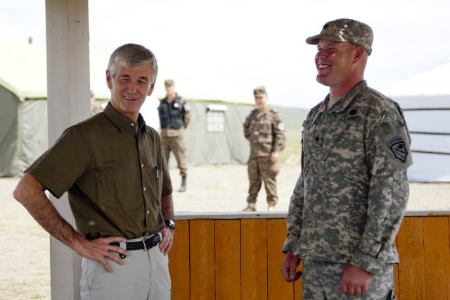 Secretary of the Army John McHugh and Spc. Joseph P. Kelly II, a medic with 1-297th Reconnaissance and Surveillance Squadron, share a light moment Aug. 15 during McHugh's visit to exercise Khaan Quest 2012, a regularly scheduled, multinational exercise in its 10th year. Kelly won the Alaska National Guard's Best Warrior Competition. (U.S. Army Photo By Spc. John G Martinez)