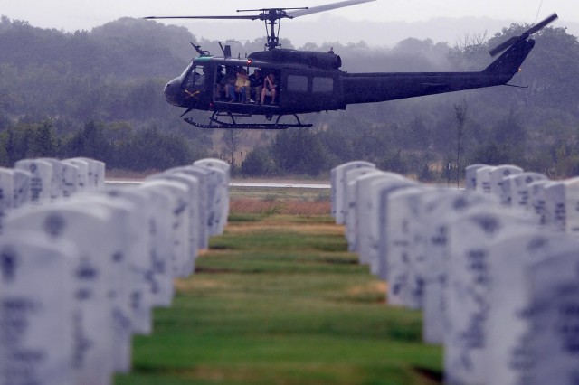 "A UH-1 helicopter, operated by 21st Cavalry Brigade (Air Combat), carries Vietnam veterans on an airlift, which passed over the Central Texas Veterans Cemetery in Killeen, Texas, Aug. 18, 2012. The flight was part of a farewell and retirement ceremony of three UH-1 ""Huey"" helicopters at Fort Hood."