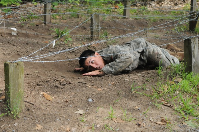 Sgt. Robert Dickey, 4th Battalion, 31st Infantry Regiment, 2nd Brigade Combat Team, crawls under barbed wire during the obstacle course event Aug. 15. Dickey was named the 10th Mountain Division's best medic.