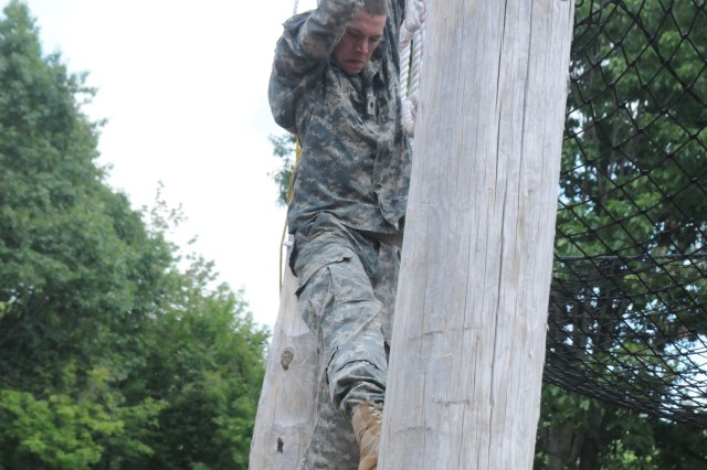 Spc. Caleb Rhodes, 5th Battalion, 25th Field Artillery Regiment, 4th Brigade Combat Team, climbs down a rope ladder using only his arms.