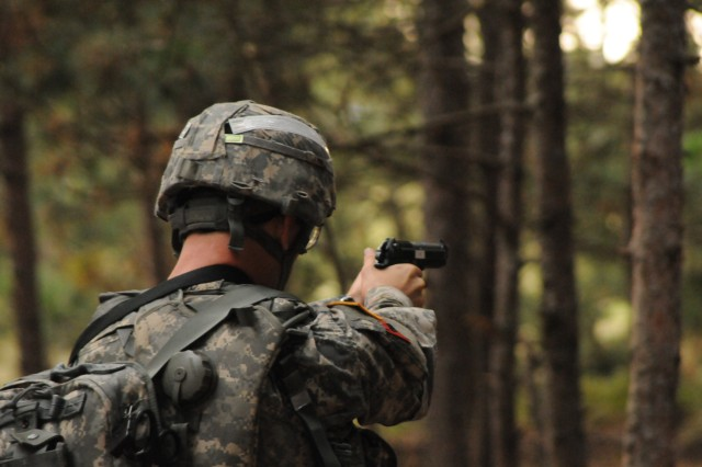 Spc. Phillip Reynolds, 3rd Squadron, 71st Cavalry Regiment, 3rd Brigade Combat Team, fires an M9 pistol at targets.