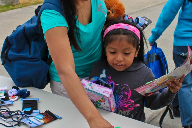 "LAKEWOOD, Wash. "" Spc. Isabel Acosta, a supply specialist assigned to the 585th Engineer Company, located at Joint Base Lewis-McChord, Wash., and her daughter Ashley Acosta look through notepads to add to their backpack full of donated school supplies during Operation Homefront's  'Back-to-School Brigade' program, at Clover Park Technical College in Lakewood, Wash., Aug. 19.  More than 800 backpacks full of school supplies donated by the community were given to military families during the distribution event."