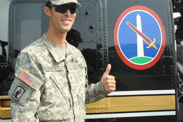 Chief Warrant Officer 2 David E. Crockett, 12th Aviation Battalion, Army Air Operations Group, Joint Force Headquarters-National Capital Region and the U. S. Army Military District gives a thumbs-up while standing next to an MDW logo on the side of a VH-60 helicopter.