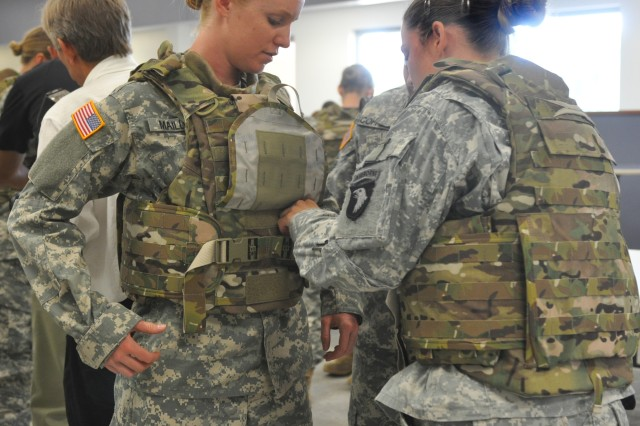 Spc. Arielle Mailloux gets some help adjusting her protoype Generation III Improved Outer Tactical Vest from Capt. Lindsey Pawlowski, Aug. 21, 2012. Both Soldiers are with the 1st Brigade Combat Team Female Engagement Team, 101st Airborne Division (Air Assault). These prototypes designed specifically for the needs of female Soldiers, with shorter torso length and other improvements, are being fielded at Fort Campbell, Ky., for the next few weeks.