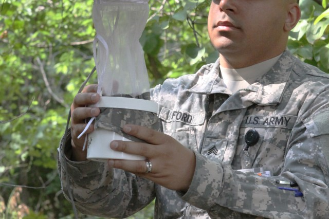 Sgt. Brendan Ford, Environmental Health Department NCOIC, checks a mosquito trap near Martha Songbird Park here. Mosquitoes are lured to the traps and then sucked in by a fan that traps them in a net so they can be checked for West Nile virus. Ford says they haven't captured many mosquitoes recently due to the extreme heat and dryness at Fort Sill.