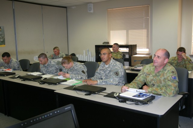 """Members of Company D, 2-13th Aviation Regiment 15W unmanned aircraft systems operator students, review their materials during the """"Unmanned Scout Operations"""" portion of common core training. The operators learn to operate UAS on Fort Huachuca because both the weather and restricted air space create favorable aircraft flight conditions."""