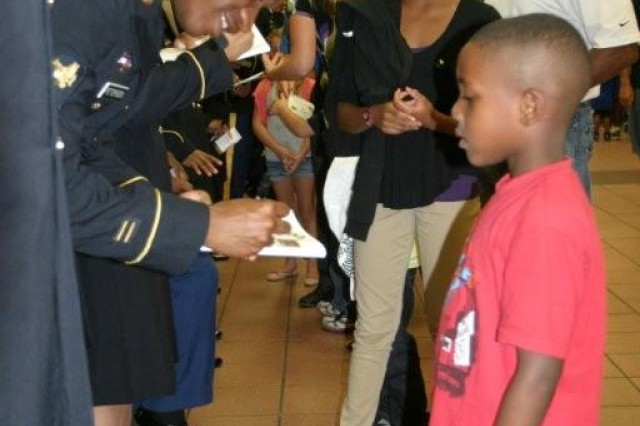 Spc. Julio Petersen III, human resource specialist, autographs a Soldier Show program for Christopher Harris, 6, after the 2012 U.S. Army Soldier Show, Monday night.