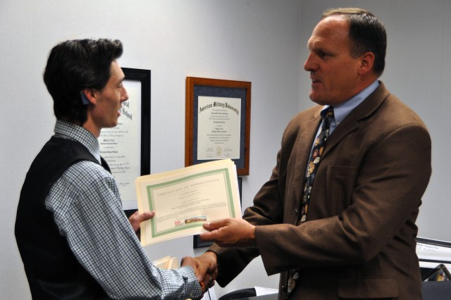 Bill Rogers, district counsel, presents Hamilton with a certificate of appreciation for his summer service to the Middle East District.