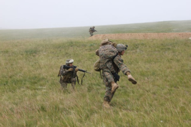 A U.S. Marine picks up a fellow Marine during a dismounted counter-improvised explosive device, or IED, training lane at Five Hills Training Area, Mongolia, during exercise Khan Quest, held Aug. 11-23, 2012. The Marines from 4th Marine Regiment based on Okinawa, were reacting to a complex IED attack and had to respond with evacuation of simulated casualties. Khan Quest is a U.S. Army Pacific sponsored exercise conducted annually with the Mongolian Armed Forces designed to promote multinational cooperation and regional security.