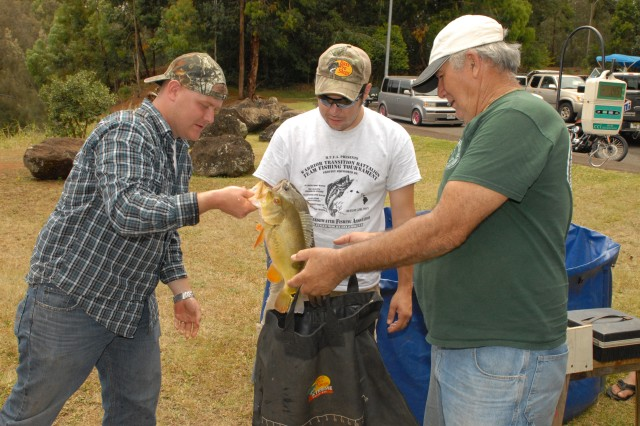 Staff Sgt. Chad McDuffee (left), Warrior Transition Battalion, Pacific Regional Medical Command, along with community members Chris Baires (middle) and Russ Wheeler, sack a Peacock Bass for the weigh-in, following the Freshwater Team Fishing Tournament, held on Lake Wilson, Wahiawa, Hawaii, Aug 5, 2012. Baires, former Soldier and the mastermind of the tournament, wanted to acknowledge the Soldiers' sacrifices. After months of planning and sponsorship from local businesses, church, and other volunteers, the event was an overwhelming success.