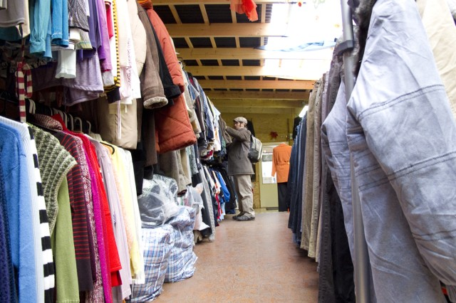 A shopper sifts through a rack of second-hand clothing at a shop on the outskirts of Prague.