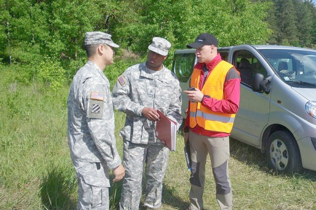 Maj. Paul Tomcik (left) and Staff Sgt. John Manurs from the 606th Senior Contingency Contracting Team, Kaiserslautern, work with a representative from the Latvian defense force during Saber Strike 2012.