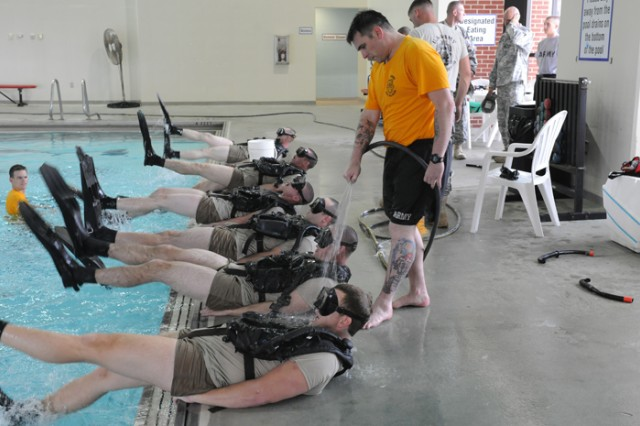 Staff Sgt. David Gills, Army Diver Phase I chief instructor, sprays water on students in the Diver Phase I course to demonstrate the value of a good fitting mask. The course is taught at Fort Leonard Wood, Mo.
