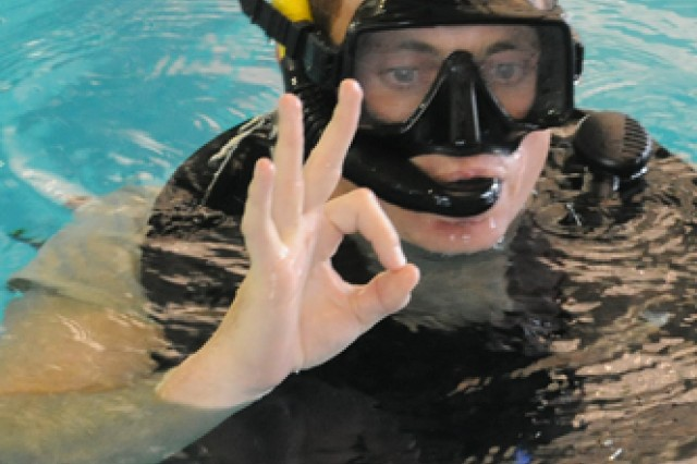 """Capt. Brian Wilson, student in the Diver Phase I course, gives the """"OK"""" sign after diving to the bottom of the pool to clear his mask at Davidson Fitness Center, Fort Leonard Wood, Mo."""