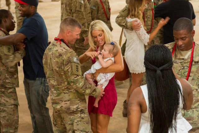 Capt. Matthew Miller, commander of 95th Engineer Company (Clearance), 65th Eng. Battalion, 130th Eng. Brigade, 8th Theater Sustainment Command, greets his wife and child following a redeployment ceremony Aug. 14 at Wheeler Gulch, Wheeler Army Airfield.