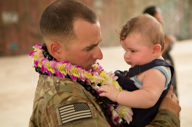 Spc. Ryan Morelock from the 95th Engineer Company (Clearance), 65th Eng. Battalion, 130th Eng. Brigade, 8th Theater Sustainment Command holds his child for the first time following a yearlong deployment to Afghanistan.  Family and friends welcomed the 95th Eng. Co. home in a redeployment ceremony Aug. 14 at Wheeler Gulch, Wheeler Army Airfield.