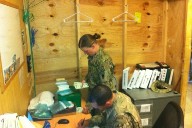 Sgt. 1st Class Dawn Ramos of the 8th Human Resources Sustainment Center counts the money received at the Army Post Office (APO) in FOB Shank during an official audit, while Sgt. Randall Myers records the results.
