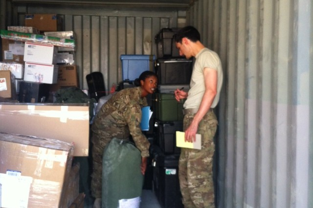 Capt. TiCondra Swartz of the 8th Human Resources Sustainment Center provides technical guidance during an official Army Post Office (APO) inspection to 1st Lt. Donald Breazeale in reference to the Postal Operations Division policy on duffel bags.