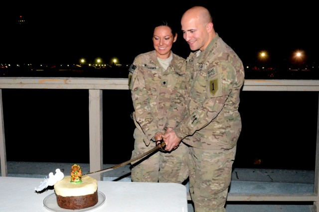 Sgt. Drew Fidler and Spc. Michelle Williams, both from Division Headquarters and Headquarters Battalion, 1st Infantry Division, stationed at Bagram Airfield, Afghanistan, cut a wedding cake at their impromptu wedding reception Aug. 25, 2012. The two were married via a double-proxy marriage through the state of Montana.