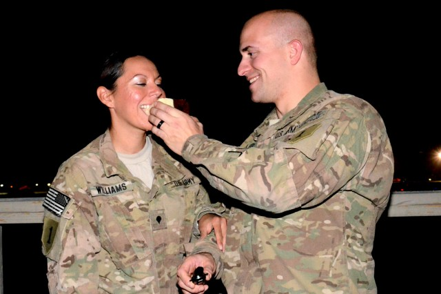 Sgt. Drew Fidler feeds his new bride, Spc. Michelle Williams, at their impromptu wedding reception, Aug. 25, 2012, at Bagram Airfield, Afghanistan. The two were married via a double-proxy marriage through the state of Montana. Both are from Division Headquarters and Headquarters Battalion, 1st Infantry Division, stationed at Bagram Airfield.