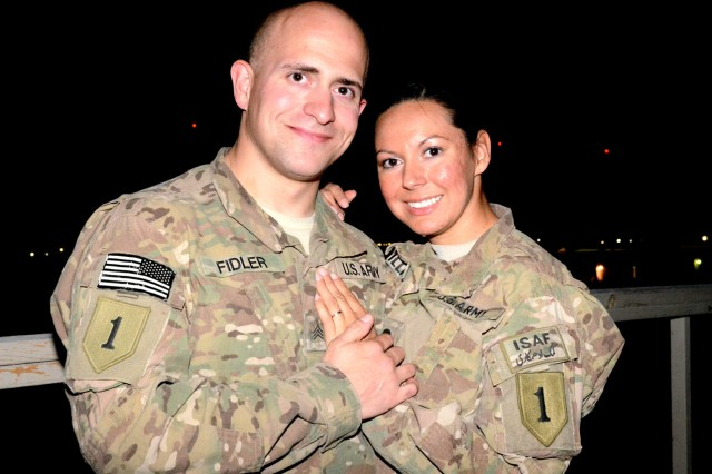Sgt. Drew Fidler and Spc. Michelle Williams, both from Division Headquarters and Headquarters Battalion, 1st Infantry Division, stationed at Bagram Airfield, Afghanistan, pose for a picture at their impromptu wedding reception Aug. 25, 2012. The two were married via a double-proxy marriage through the state of Montana.