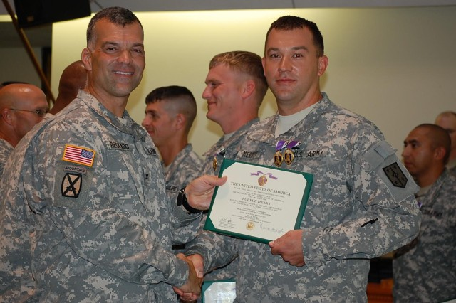 FORT LEONARD WOOD, Mo. -- Col. James F. Reckard III., commander of the 4th Maneuver Enhancement Brigade, awards Spc. Taylor Merrit, a construction equipment repairer assigned to 509th Clearance Company, 5th Engineer Battalion with two Purple Hearts during a post-deployment ceremony in Specker Chapel Aug. 9, 2012. Meritt received two awards out of 153 awards approved for 509th Clearance Company Soldiers during their deployment in support of Operation Enduring Freedom 2011 to 2012. (Photo by: U.S. Army Cpt. Jeffrey Nichols, 5th Engineer Battalion Unit Public Affairs Representative)