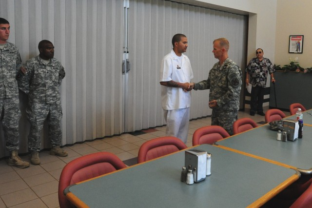 FORT CAMPBELL,Ky- U.S. Army Col. David Dellinger, the U.S. Army Garrison-Fort Campbell commander, awards Spc. James F. McCollum from Headquarters and Headquarters Company, 4th Brigade Special Troops Battalion, 4th Brigade Combat Team, 101st Airborne Division, and recipient of the title Best Cook of the Quarter, a coin for excellence, Aug. 22. 2012 during a ceremony at Fort Campbell, Ky. (U.S. Army photo by Sgt. Kimberly K. Menzies, 4th Brigade Combat Team Public Affairs)