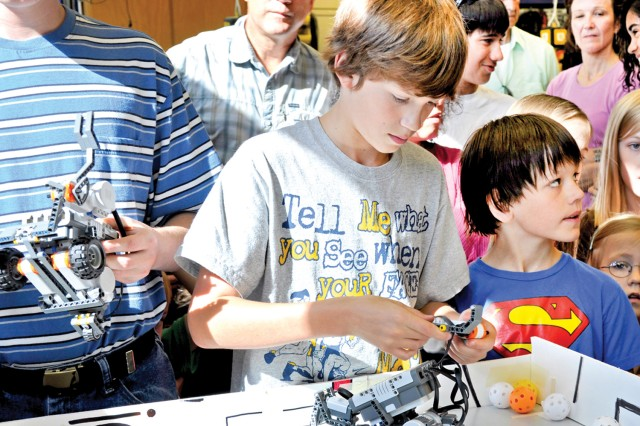 Mason Payeur, 12, works on a robot during the Robotics Summer Day Camp at Wiesbaden High School, Germany, Aug. 13-17, 2012. Students in grades seven through nine participated in the camp, which gave them an introduction to building and programming robots.