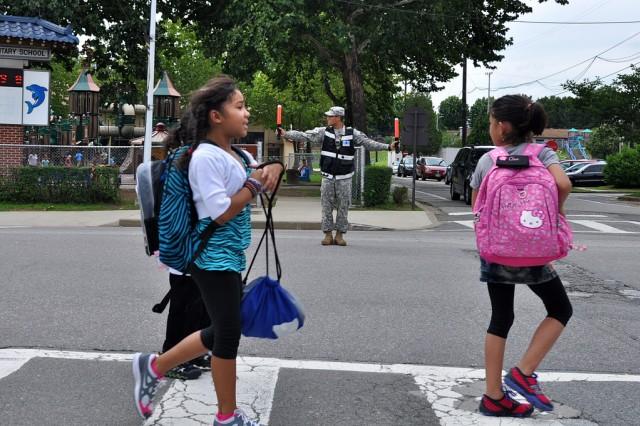 Seoul American Elementary school students cross street while MP controls traffic. (U.S. Army photo by Pfc. Lee Hyokang)