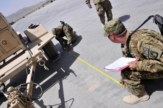 Soldiers from the 25th Combat Aviation Brigade measure a trailer to find the center of balance before it is shipped back to the states during the weighing scenario as part of the 209th Aviation Support Battalion, 25th CAB Unit Movement Officer Rodeo Competition as pre-redeployment training on Kandahar Airfield, Afghanistan, Aug. 15.