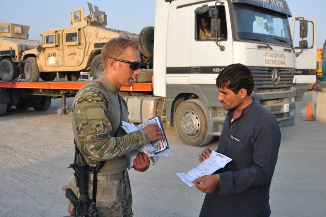 Sgt. Anthony R. Stenson, a mission commander with the 1157th Transportation Company, goes over paperwork with an Afghan truck driver on August 24, 2012 at Jalalabad Airfield. All hosts nation truck drivers must have the proper paperwork to haul cargo from a forward operating base to its destination. (U.S. Army photo by Sgt. Gregory Williams)
