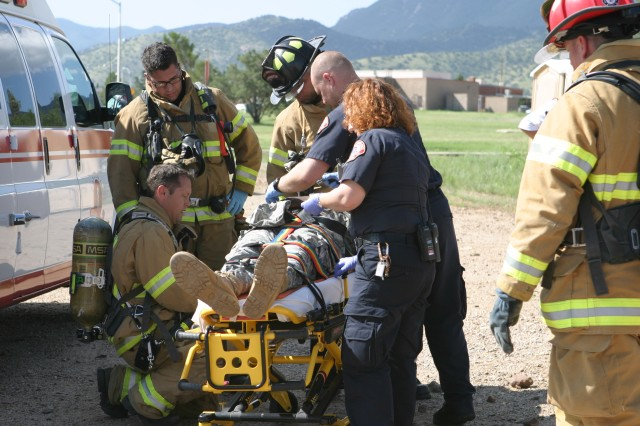 Fort Huachuca firefighters and Arizona Ambulance emergency medical technicians work together to help save the life of a role player who was wounded during a car explosion as part of the force protection exercise on Fort Huachuca Tuesday morning. FPXs help ensure Fort Huachuca personnel are ready to effectively respond in an emergency situation.