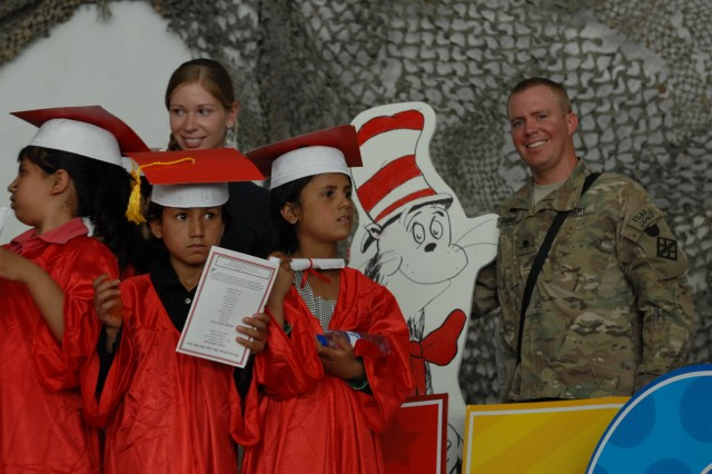 Spc. Taylor A. Daniel, logistics coordinator for the 411th Engineer Brigade, Joint Task Force Empire, stands with students after a ceremony where 43 Bagram youths became the first class to graduate from the Cat in the Hat Language Arts Center at Bagram Air Field, Afghanistan, Aug. 26, 2012.  Daniel, an Athens, Ga. native, volunteers at the school and said he sees the center as one way to build the country up from a children's perspective.