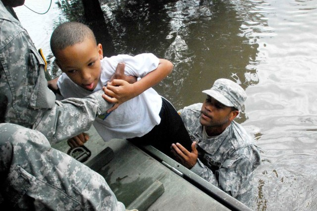 Army Sgt. Lee Savoy, assigned to the Louisiana Army National Guard's 256th Brigade Special Troops Battalion, assists with getting a child onto the back of one of the unit's trucks as Soldiers from the unit work to rescue local residents from flood waters caused by Hurricane Isaac, Aug. 30. The Louisiana National Guard has more than 8,000 Soldiers and Airmen ready to support local and state authorities in support of Hurricane Isaac relief operations.