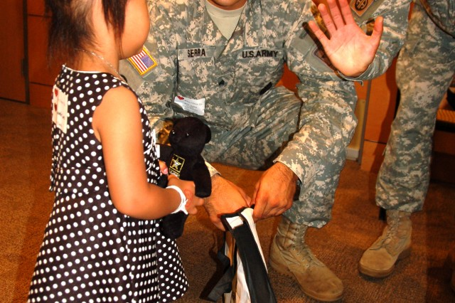 "Sgt. Carlos Serra gives Annabelle Lee an Army Teddy Bear, as Staff Sgt. Andres Valencia offers a high-five at the annual ""When I Grow Up"" event on Aug. 4, 2012, for children with heart conditions."