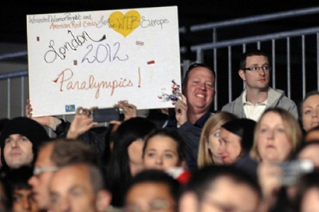 Sgt. Justin Camp, a chemical specialist assigned to Company A, Warrior Transition Battalion in Europe, holds up a poster made by the Red Cross supporting U.S. Paralympic athletes during the Paralympic Games judo competition at the ExCel Centre in London, Aug. 30, 2012.