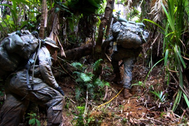 U.S. Soldiers trudge up a stream bank during the 12-day Australian Army Junior Leader Jungle Training Course, held from July 30 to Aug. 10, 2012, in Queensland, Australia.  Recent cyclones had ravaged the jungle canopy, littering the ground with debris and vegetation so thick it was impossible to walk through in spots.