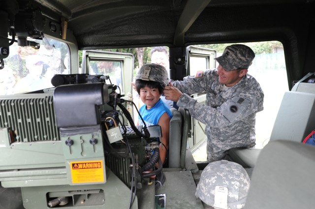 Staff Sgt. Christopher Hogan, assigned to U.S. Army Japan's I Corps (Forward), places a helmet on the head of a child seated in a Humvee during the Sagamihara City Disaster Drill, held Sept. 2, 2012, at Fuchinobe Park in Sagamihara City, Japan. More than 1,200 people took part in the annual exercise.